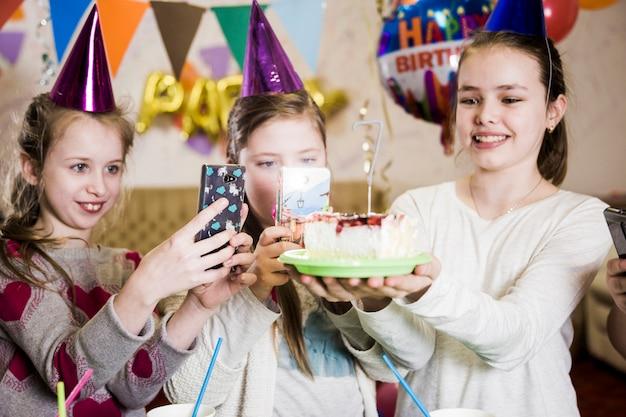 Meninas tirando fotos de bolo