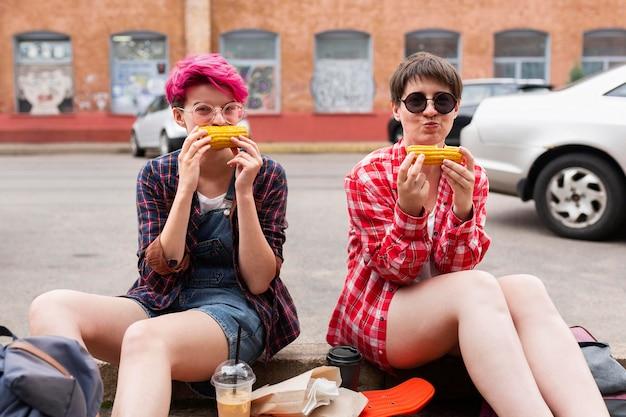 Meninas tiro completo, comendo milho