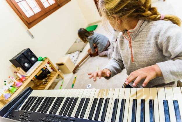 Meninas tocando piano na aula de música.