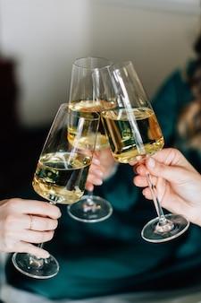 Meninas torcendo com champanhe. copos de vinho tilintando