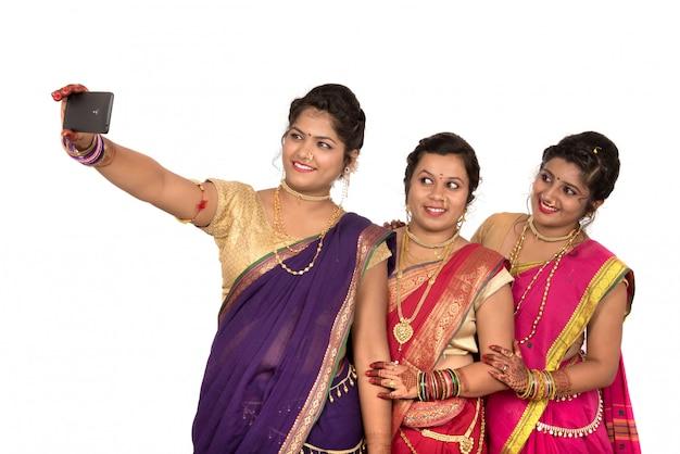 Meninas tradicionais indianas tomando selfie com smartphone em fundo branco