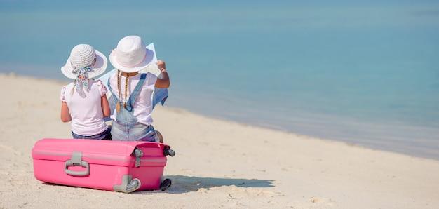 Meninas turistas com mala grande na praia branca tropical