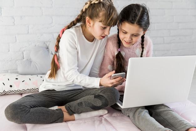 Meninas, usando computador portátil, junto