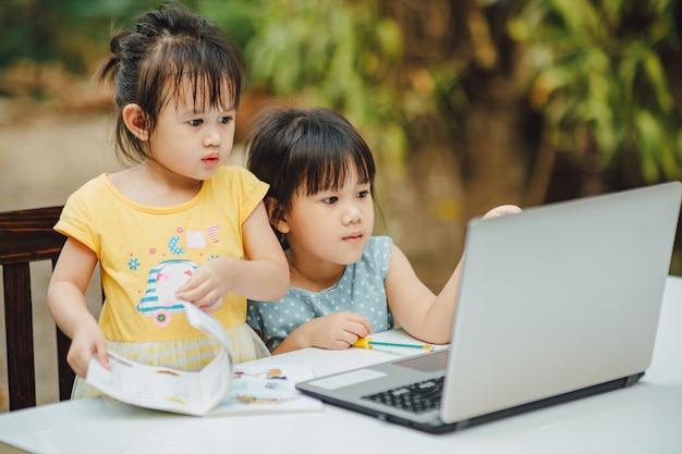 Meninas usando o computador portátil
