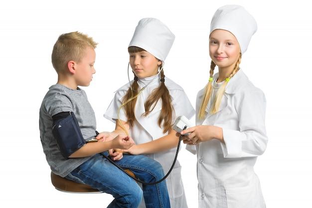 Meninas vestidas como médicos medindo a pressão arterial do menino