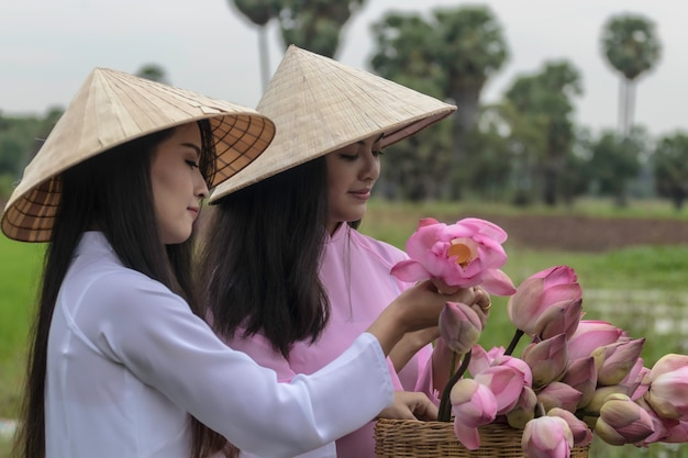 Meninas vietnamitas que vestem o vestido nacional e que dobram flores de lótus em uma bicicleta.
