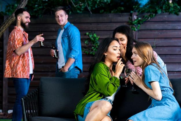 Meninas vista frontal com bebidas fofocando