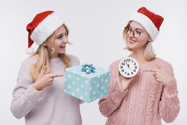 Meninas vista frontal, segurando uma caixa de presente