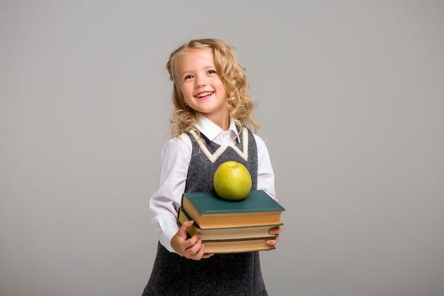 Menininha com livros sobre um fundo claro