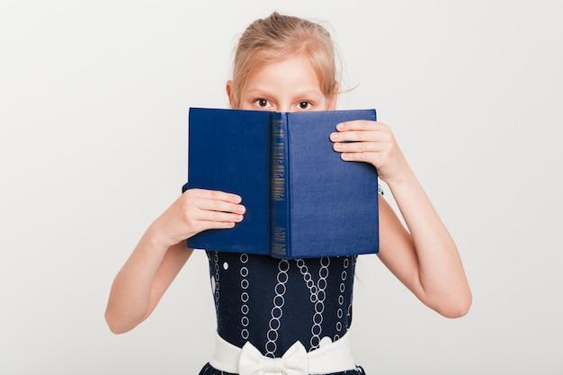Menininha, com, rosto, atrás de, livro