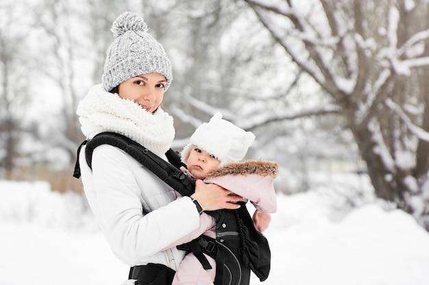 Menininha, dela, mãe, andar, exterior, em, inverno mãe, segurando, bebê, babywearing