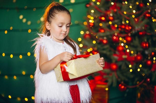 Menininha, desembrulhando, presente, por, árvore natal