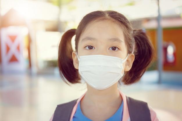 Menininha, em, uniforme escola, desgastar, um, máscara cirúrgica, com, fundo obscurecido