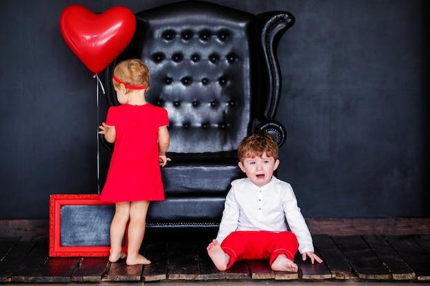 Menininha loira de vestido vermelho com coroa vermelha com corações e menino