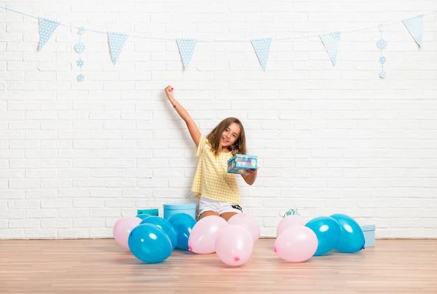 Menininha loira em uma festa de aniversário fazendo gesto de vitória