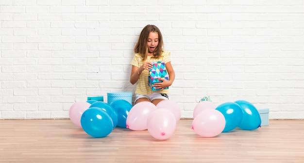 Menininha loira em uma festa de aniversário fazendo gesto surpresa