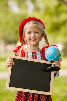 Menininha loira primeira série no vestido vermelho e boina segurando uma prancheta vazia e globo