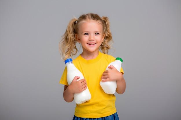 Menininha loira segurando garrafas de plástico de leite