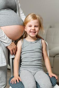 Menininha, sentando, perto, mãe, barriga grávida
