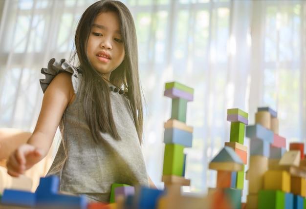 Menininha, tocando, com, construção, brinquedo bloqueia, predios, um, torre