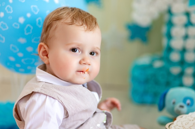 Menino 1 ano com um bolo e balões, aniversário de uma criança 1 ano, bebê come bolo