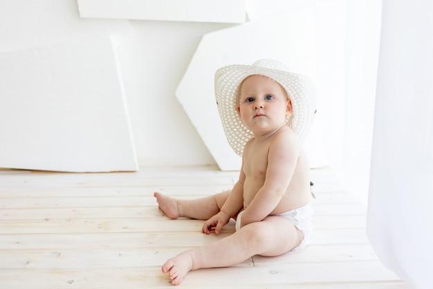 Menino 8 meses de idade, sentado em fraldas com um chapéu branco na janela