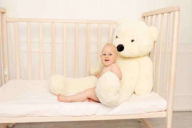 Menino 8 meses de idade, sentado em fraldas em um berço com um grande urso de pelúcia no berçário