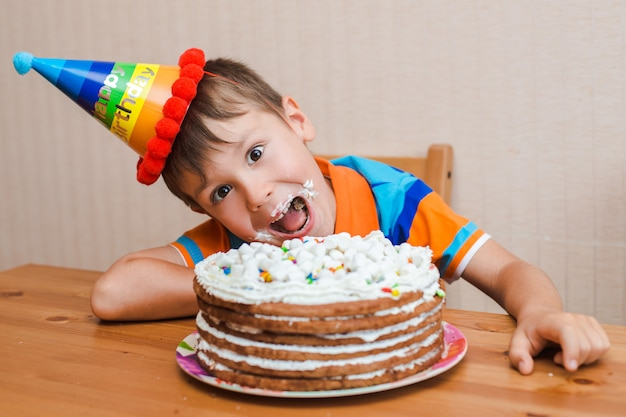 Menino a criança está comendo seu bolo de aniversário.