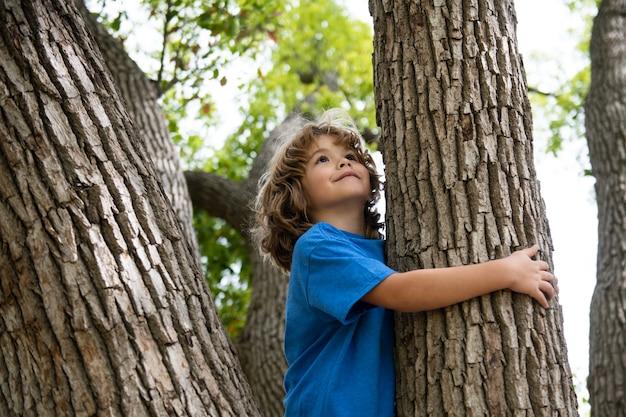 Menino abraçando um galho de árvore menino menino em um galho de árvore criança sobe em uma árvore
