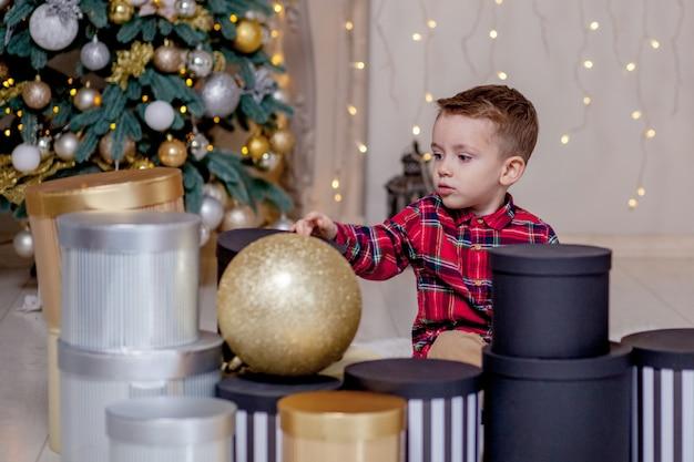 Menino abrindo presentes no dia de natal