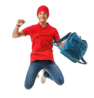 Menino adolescente afro-americano pulando com mochila no fundo branco
