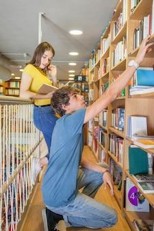 Menino adolescente, alcançar, prateleira, enquanto, procurar, livro, perto, namorada