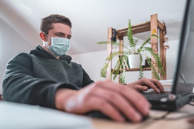 Menino adolescente ativo na máscara facial com trabalhos de casa do portátil durante a quarentena do coronavírus.