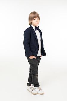 Menino adolescente bonito em traje preto fica isolado no fundo branco