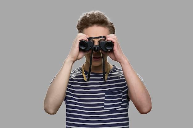 Menino adolescente caucasiano olhando através dos binóculos. curioso adolescente usando binóculos em pé contra um fundo cinza.