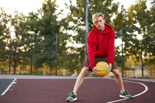 Menino adolescente caucasiano realizando manobras com uma bola de basquete no campo de esportes