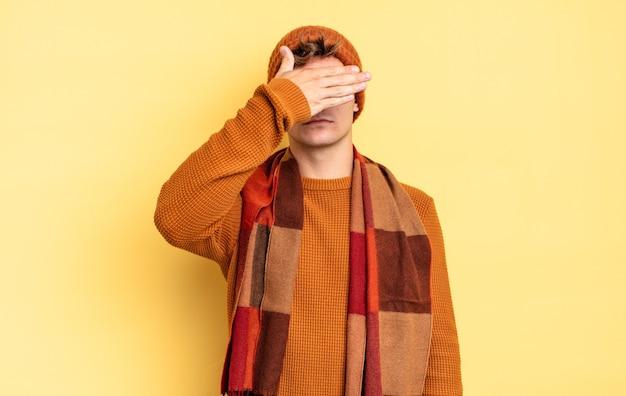 Menino adolescente cobrindo os olhos com uma das mãos, sentindo-se assustado ou ansioso, imaginando ou esperando cegamente por uma surpresa