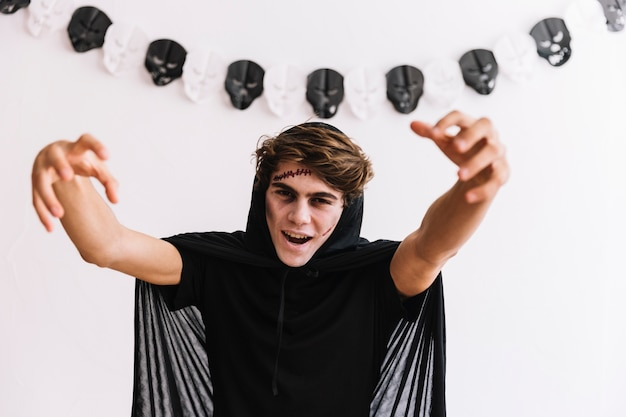 Menino adolescente, com, dia das bruxas, desagradável, em, capa preta, fazendo, assustador, gestos