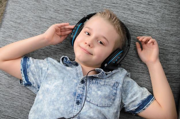 Menino adolescente com fones de ouvido ouve música no sofá em casa adolescente curtindo música menino loiro enquanto está deitado no sofá