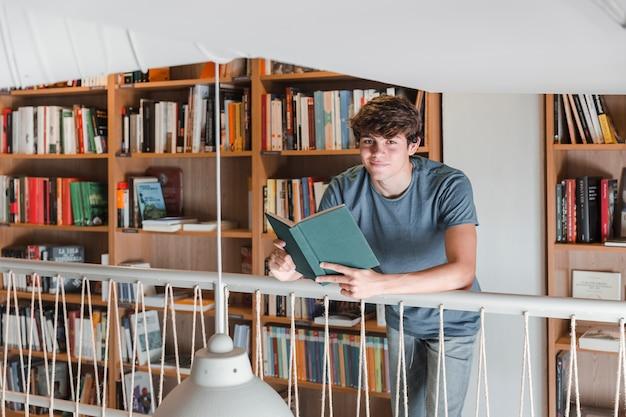 Menino adolescente, com, livro, olhando câmera