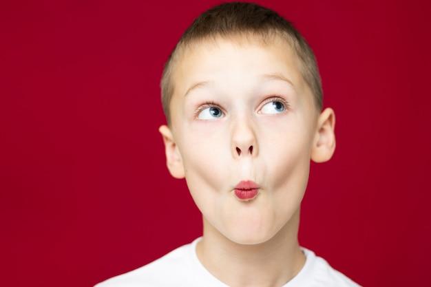 Menino adolescente de 7 a 10 anos em uma camiseta branca fazendo caretas, retratando um beijo