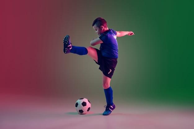 Menino adolescente de futebol ou jogador de futebol em um fundo gradiente em atividade de ação de movimento de luz de néon