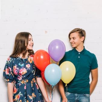 Menino adolescente, e, menina, segurando balões, em, mão, olhando um ao outro