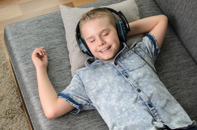 Menino adolescente elegante ouvindo música em fones de ouvido e cantando em casa menino feliz e sorridente descansando no sofá em casa