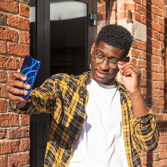 Menino adolescente em tiro médio tirando uma selfie