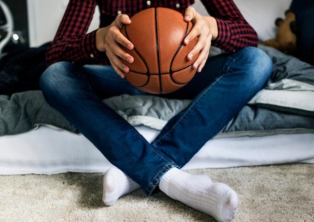 Menino adolescente, em, um, quarto, segurando, um, basquetebol, passatempo, aspiração, e, solidão, conceito
