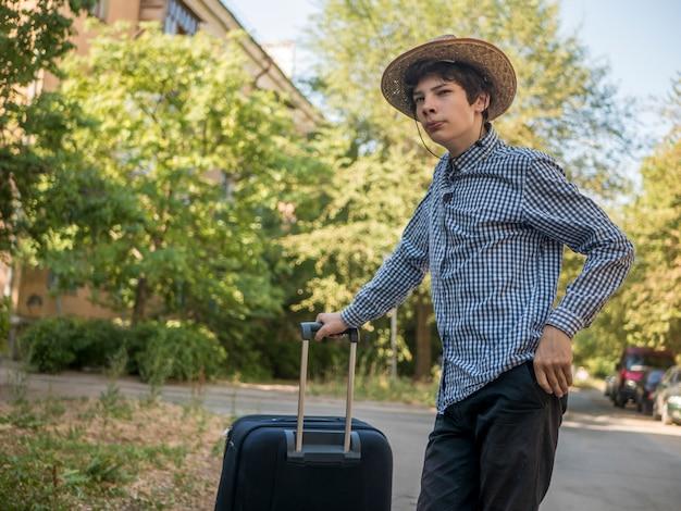 Menino adolescente, em, verão, chapéu, viajando, com, grande, bagagem, saco