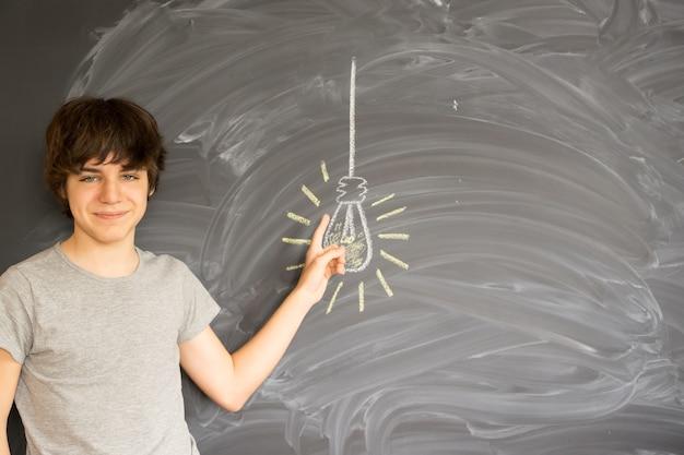 Menino adolescente encontrando uma ideia e apontando na lâmpada - conceito de educação de volta à escola