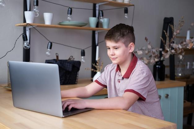 Menino adolescente estudando online, jogando videogame usando laptop sentado na cozinha.