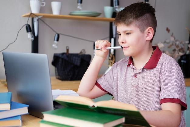 Menino adolescente estudando online usando o laptop, lendo um livro na cozinha em casa.